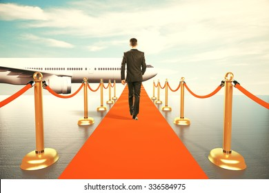 Businessman walking on red carpet to the first class of plane