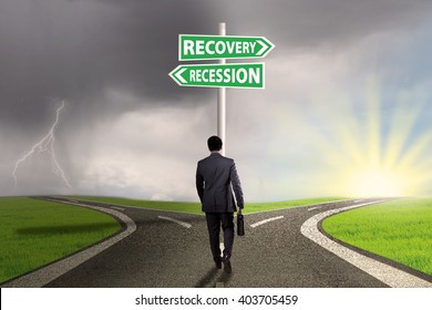 Businessman walking on the road with two words of recession and recovery on the signpost pointing the way