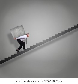 Businessman walking on stairs up fprwards while carrying heavy stone load on his back, failure adversity in business concept