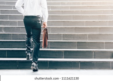 Businessman walking up on stairs and holding briefcase.