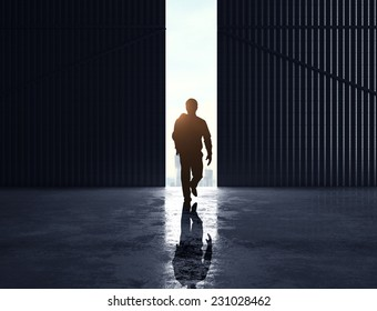 businessman walking to open gate