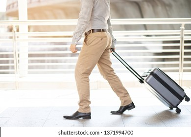 businessman walking outside public transport building with luggage in rush hour. Business traveler pulling suitcase in modern airport terminal. baggage business Trip.  Copy space