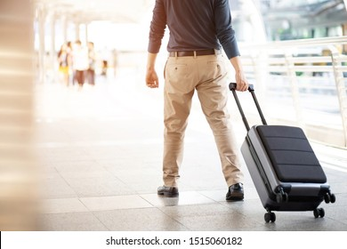 businessman walking outside public transport building with luggage in rush hour. Business traveler pulling suitcase in modern airport terminal. baggage business Trip.
