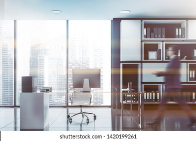 Businessman walking in panoramic CEO office with black walls, white bookcase and glass computer table. Toned image blurred