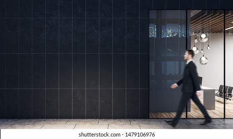 Businessman walking past dark wall business center with modern light conference room with wooden floor and black chairs.