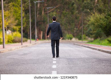 Businessman walking in the road line