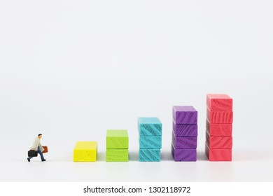 businessman walking or running to company graph (stacking wood block)