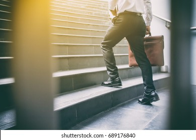 Businessman walking up the stairs hastily. In his hand is a brown leather briefcase. with flare light.