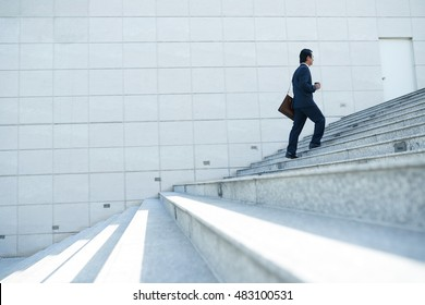 Businessman walking up the stairs, side view