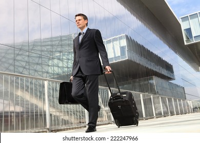 businessman walking with trolley and bag, business travel