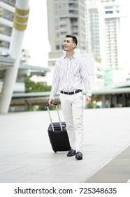 The  businessman walking  with white shirt on business trip with suitcase.