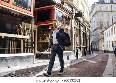 Businessman is walking to work in the city. He is wearing trainers and carrying a gym bag over his shoulder.