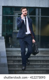A businessman walks down the stairs and talking on mobile phone holding a briefcase against the building with a glass facade