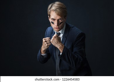 Businessman with war paint on his face. Risk management concept. young guy in suit with tie is ready to fight, black background