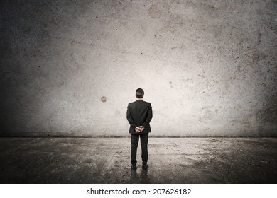 businessman watching a empty scratched wall