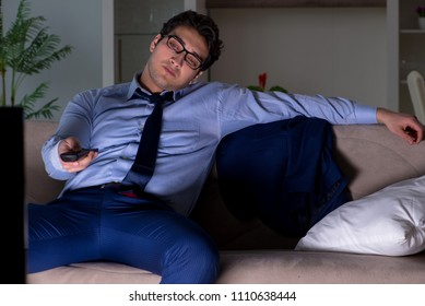 Businessman watching tv at night late