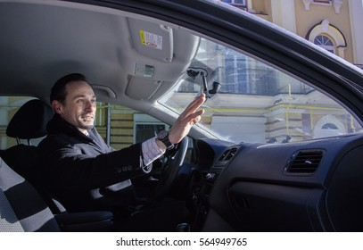 Businessman waving someone out of the car by his hand, outdoor, day . Man talking to friends from his driver sit