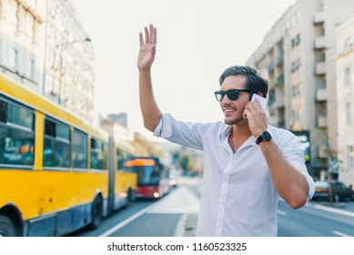 Businessman waving for a taxi in busy city. Handsome Man with Sunglasses is Stopping a Taxi in the City Center. A handsome young businessman waving for a taxi. Pick up a ride