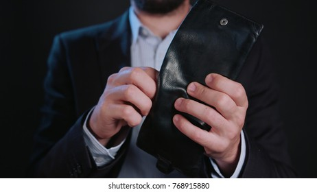A businessman wearing a black jacket and a white shirt taking cash (Euros) out of his wallet against a black background. Close-up shot