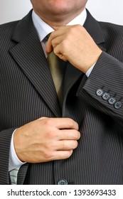 Businessman wearing black suit doing tie