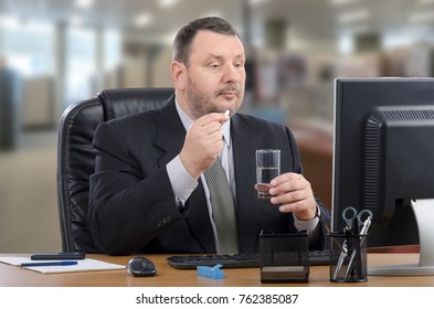 Businessman wearing black suit holds white pill with right hand sitting in front of computer monitor in the office. Bearded man consults e-health doctor during lunch time. Blurred indoors background