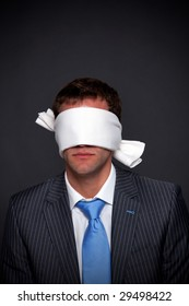 Businessman wearing a blindfold on a dark background with copy space.