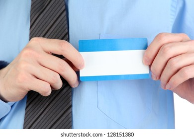Businessman wearing blue shirt with tie and holding blank nametag close up