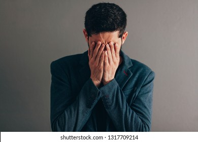 businessman wearing blue suit with sad expression covering face with hands while crying. Depression concept.