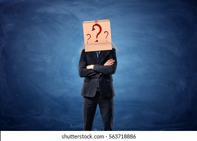Businessman is wearing a cardboard box with drawn question marks on his head on blue chalkboard background. Decision making. Business problems. Anonymous person.