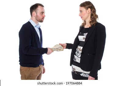 Businessman wearing dark blue sweater handing money to woman on white background.