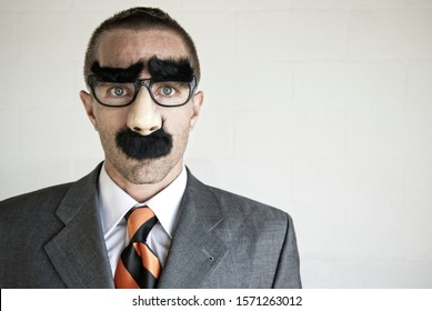 Businessman wearing a disguise of glasses with thick eyebrows and mustache looking at camera with blank expression