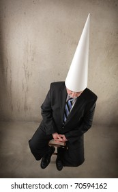 Businessman wearing a dunce cap