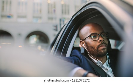 Businessman wearing earphones and listening musing while driving a car. African businessman being stuck in morning traffic.