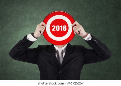 Businessman wearing formal suit while covering his face with number 2018 on the dartboard