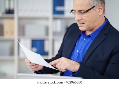 Businessman wearing glasses sitting at his desk in the office carefully reading a paper document