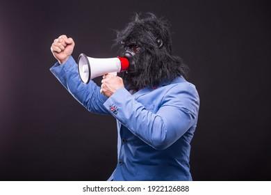 businessman wearing gorilla mask and screaming to megafon