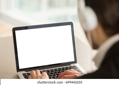 Businessman wearing headphones working on pc laptop with mock up white blank empty screen, copy space for product placement, online audio course, business services ads, close up, focus on screen