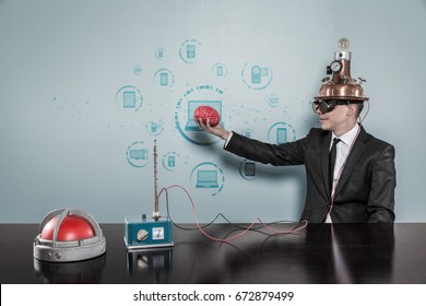 Businessman Wearing Helmet Holding Brain By Connecting Laptops Text