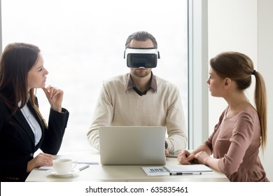 Businessman wearing innovative vr headset for laptop at business meeting. Business team developing virtual reality applications, future realistic technology on computer for business concept