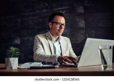Businessman wearing linen suit and eyeglasses sitting at his desk and using laptop in the office