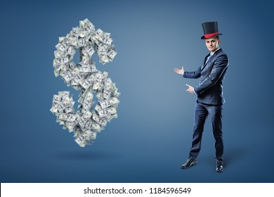 A businessman wearing a magician's hat and presents a large dollar sign made of many bills. Money and prosperity. Easy money. Get rich with simple trick.
