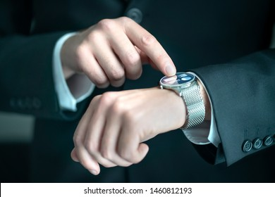Businessman wearing smart watch with banking, finance or business report app. Man in suit using wearable gadget for work. Hybrid smartwatch with touch screen and metal band. People with wearables.