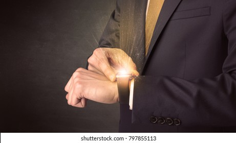 Businessman wearing smartwatch with shiny rays on it.