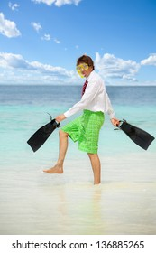 Businessman wearing snoring mask with flippers and wearing formal clothes with red tie entering water on the beach