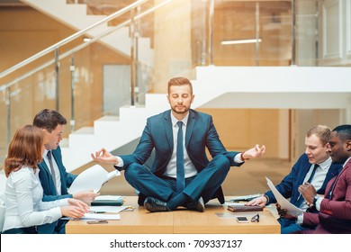 Businessman wearing a suit doing Yoga on the table and other businessmans angry.