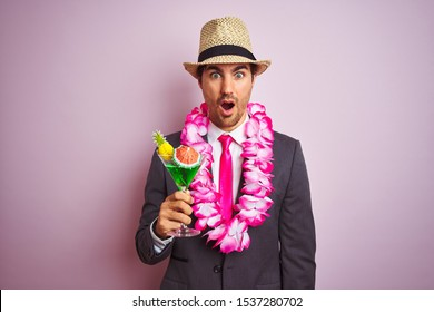 Businessman wearing suit hat hawaiian lei drinking cocktail over isolated pink background scared in shock with a surprise face, afraid and excited with fear expression