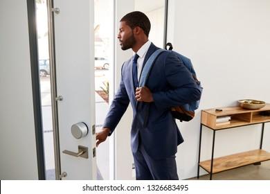 Businessman Wearing Suit Opening Door Leaving Home For Work