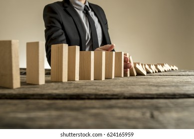 A businessman wearing a suit standing beside a series of vertical wooden slabs as they fall one after another. Concept of domino effect where one business failure causes further collapses.