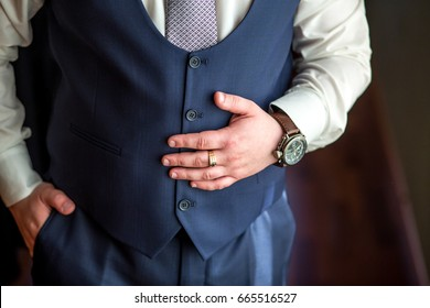 Businessman wearing suit, vest, tie holding hand on a stomach, detail