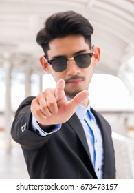 Businessman wearing sunglass and point finger (selective focus)